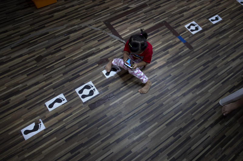 Phatramon Thongthad, a daughter of a teacher of Makkasan preschool, plays with her mobile phone on a floor marked with physical distancing guidelines at the preschool in Bangkok, Thailand, Wednesday, June 24, 2020. The teachers, many of whom are from the community, are eager to have the children back in the classroom but recognize the challenges posed by social distancing active preschoolers in a compact facility in this densely populated community. (AP Photo/Gemunu Amarasinghe)
