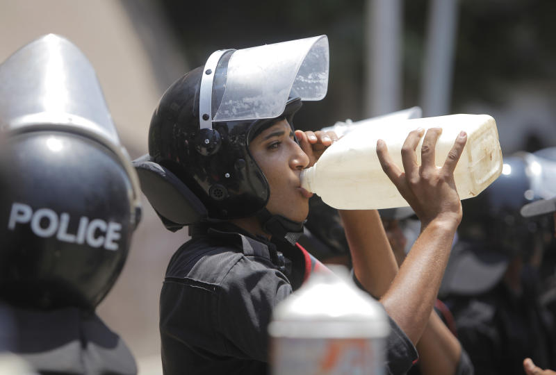 An Egyptian anti-riot soldier drinks water as he stands alert in front the State Council ahead of an anticipated Administrative Court ruling on the panel writing the new constitution in Cairo, Egypt, Thursday, July 19, 2012. (AP Photo/Amr Nabil)