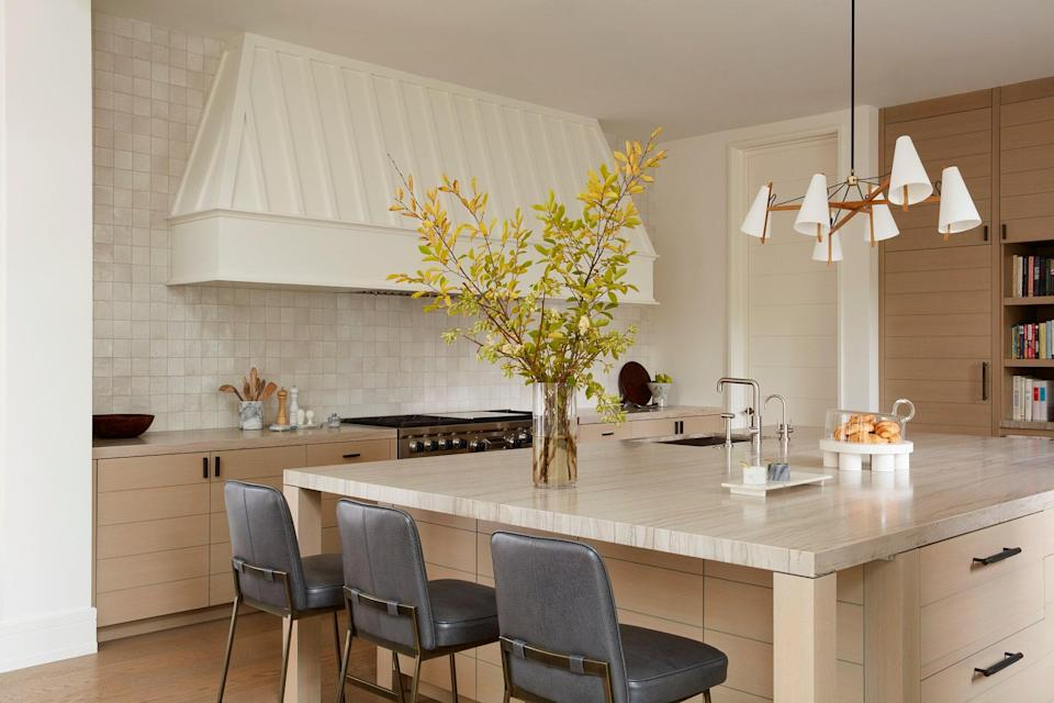The soothing kitchen comes to life by way of an Ann Sacks tile backsplash and a Brendan Ravenhill Long Hood Chandelier. Three Lawson-Fenning Elysian barstools sit along the kitchen island.