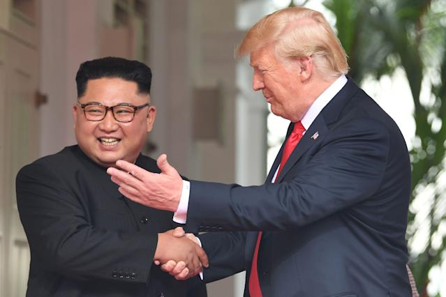 <p>US President Donald Trump (R) shakes hands with North Korea's leader Kim Jong Un as they meet at the start of their historic US-North Korea summit, at the Capella Hotel on Sentosa island in Singapore on June 12, 2018. – Donald Trump and Kim Jong Un have become on June 12 the first sitting US and North Korean leaders to meet, shake hands and negotiate to end a decades-old nuclear stand-off. (Photo: Saul Loeb/AFP/Getty Images) </p>