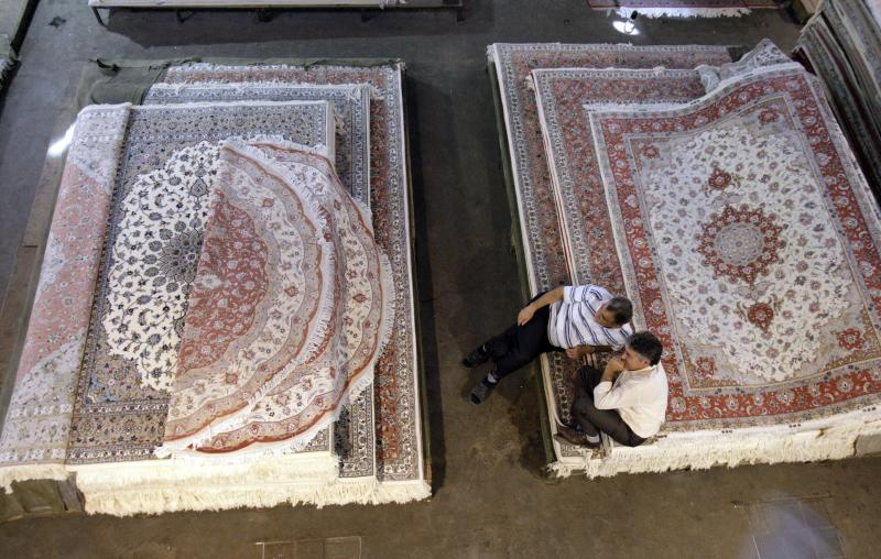 Iranian carpet sellers wait for customers at Tehran's old main bazaar in downtown Tehran, Iran, Sunday, Oct. 7, 2012. Iran's parliament on Sunday abandoned its planned impeachment of a Cabinet minister over the free-fall of the country's currency, opting instead to look for more effective economic measures, like cutting spending. The aborted move to impeach the minister reflects unease over the severe drop in the value of the Iranian rial, mostly because of Western sanctions over Iran's suspect nuclear program. On Sunday the parliament approved outlines of a bill to restrict the government's use of different exchange rates for its foreign revenue and requiring the return of some funds to the treasury. (AP Photo/Vahid Salemi)