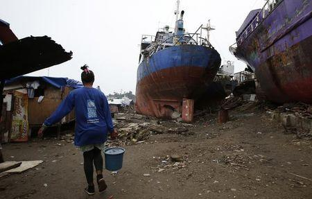 A typhoon survivor carries a pail of water towards a temporary shelter in Tacloban city