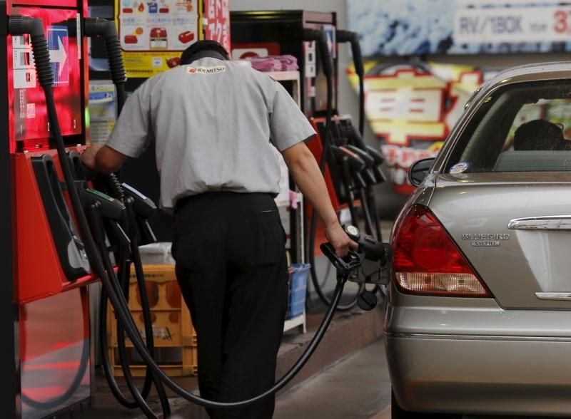 A gas station worker fuels a vehicle in Tokyo