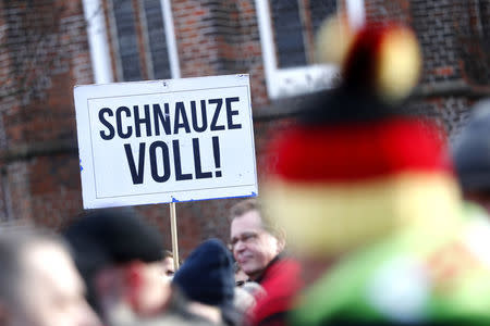 """A man holds a placard during the demonstration against migrants in Cottbus, Germany February 3, 2018.  Sign reads """"Fed up!"""". REUTERS/Hannibal Hanschke"""
