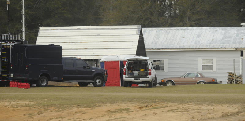 Law enforcement personnel station themselves on the property of Jimmy Lee Sykes, Monday, Feb. 4, 2013 in Midland City, Ala. Officials say they stormed a bunker in Alabama to rescue a 5-year-old child being held hostage there after Sykes, his abductor, was seen with a gun. (AP Photo/AL.com, Joe Songer)