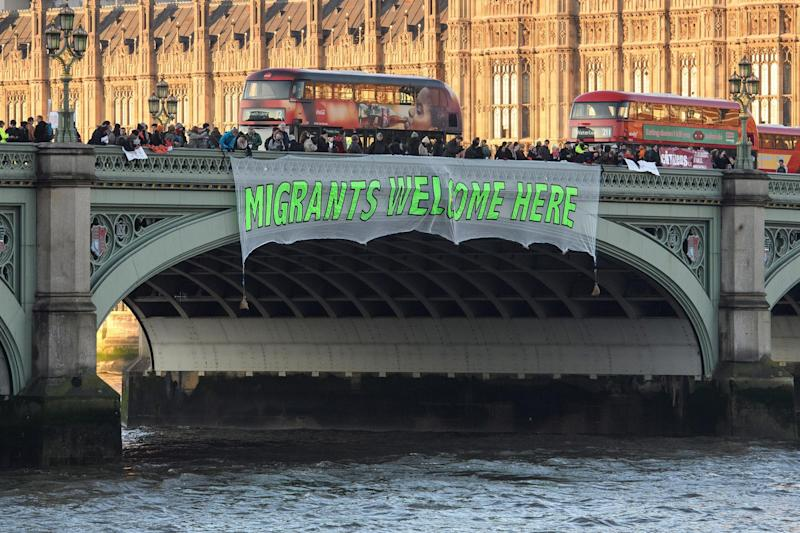 A banner reading 'Migrants Welcome Here' is unfurled on Westminster Bridge on January 20, 2017 in London