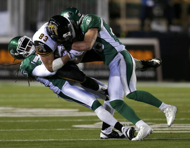 Hamilton Tiger-Cats Andy Fantuz (83) is tackled by Saskatchewan Roughriders Dwight Anderson (33) and Craig Butler (28) during the second half of the CFL's 101st Grey Cup championship football game in Regina, Saskatchewan November 24, 2013. REUTERS/Todd Korol (CANADA - Tags: SPORT FOOTBALL)