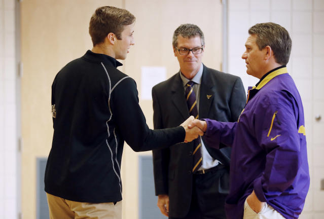 Minnesota State, Mankato defensive back Sam Thompson left, shakes hands with coach Todd Hoffner, as athletic director Kevin Buisman watches on Thursday April 17, 2014, in Mankato , Minn. Players ended their boycott of spring practice and said Thursday they will play for Hoffner, who was reinstated after being exonerated of having child pornography on his cellphone. (AP Photo/Star Tribune, Jerry Holt)
