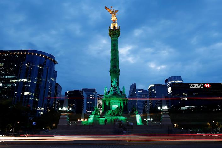 Green lights are projected at the Angel of Independence monument in Mexico City. (Photo: Carlos Jasso/Reuters)