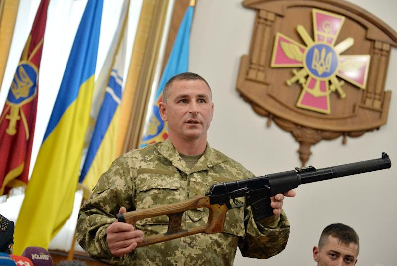A Ukrainian officer shows a special nine-millimetre calibre rifle seized from captured Russian servicemen, during a press conference in the Ministry of Defence of Ukraine in Kiev on May 18, 2015 (AFP Photo/Genya Savilov)