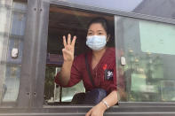 In this image made from video, a woman flashes the three-fingered salute from a vehicle as a crowd of protesters march past Saturday, Feb. 6, 2021, in Yangon, Myanmar. The military authorities in charge of Myanmar broadened a ban on social media following this week's coup, shutting access to Twitter and Instagram, while street protests continued to expand Saturday as people gathered again to show their opposition to the army takeover. (AP Photo)