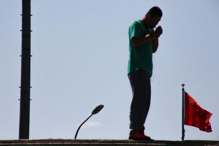 A man lights a cigarette near the Chinese national flag in Beijing