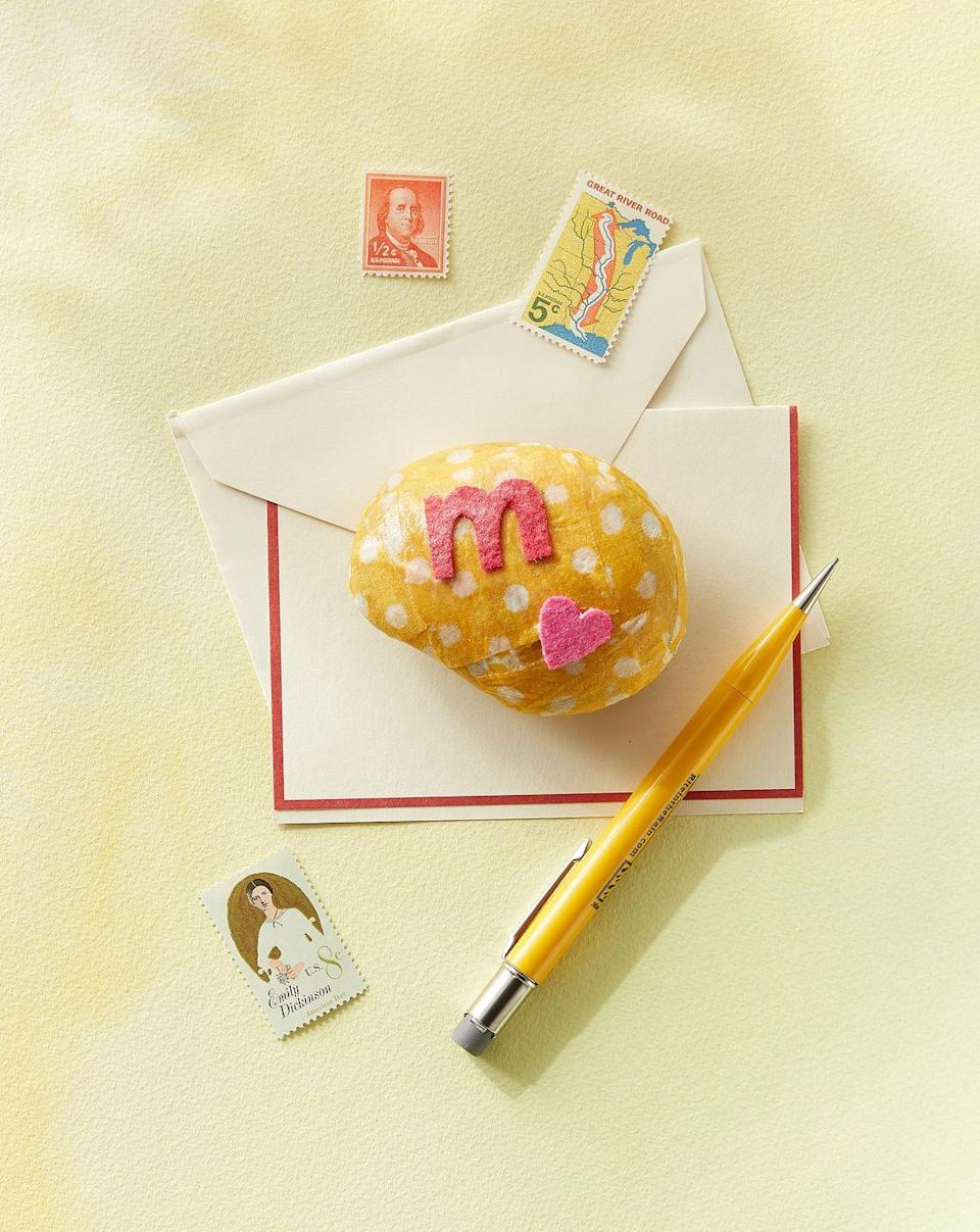 """<p>Make mom's desk pretty with a personalized paperweight. Start by cutting fabric into strips. Adhere to a small rock (2 to 3 inches) with glossy Mod Podge. Cut an initial and a heart from felt and adhere to the top of the rock. Allow to dry completely.</p><p><a class=""""link rapid-noclick-resp"""" href=""""https://www.amazon.com/CS11201-Mod-Podge-8-Ounce-1-Pack/dp/B003W0XR8M/?tag=syn-yahoo-20&ascsubtag=%5Bartid%7C10050.g.2357%5Bsrc%7Cyahoo-us"""" rel=""""nofollow noopener"""" target=""""_blank"""" data-ylk=""""slk:SHOP MOD PODGE"""">SHOP MOD PODGE</a></p>"""