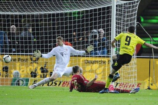Bayern Munich's goalkeeper Manuel Neuer (L) misses a goal scored by Dortmund's striker Robert Lewandowski (R) during the German cup final at the Olympiastadion in Berlin. Dortmund won 5-2