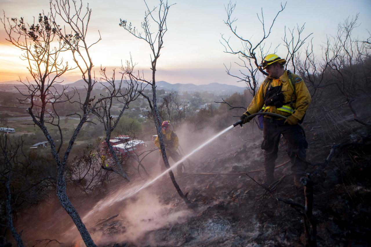 Fire crew put out smouldering embers from the Cocos Fire in San Marcos, California May 15, 2014. A towering wall of flames charged a hillside California community on Thursday as firefighters battled fierce wildfires that have forced 125,000 people to flee homes in the San Diego area and may have killed at least one person. REUTERS/Sam Hodgson (UNITED STATES - Tags: ENVIRONMENT DISASTER TPX IMAGES OF THE DAY)