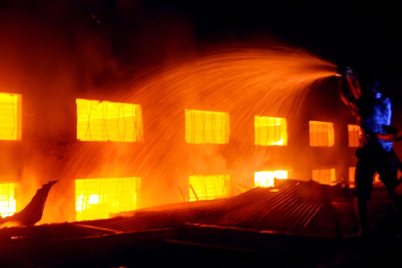 A Bangladeshi firefighter battles a fire at a garment factory ioutside Dhaka, Bangladesh, Saturday, Nov. 24, 2012. At least 112 people were killed in a fire that raced through the multi-story garment factory just outside of Bangladesh's capital, an official said Sunday. (AP Photo/Hasan Raza)