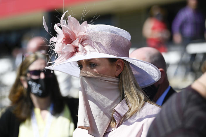 A woman wears a face covering to protect against the spread of COVID-19 during the Preakness Stakes horse race at Pimlico Race Course, Saturday, May 15, 2021, in Baltimore. (AP Photo/Nick Wass)