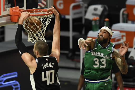 Los Angeles Clippers center Ivica Zubac, left, dunks past Dallas Mavericks center Willie Cauley-Stein during the first half of an NBA basketball game in Los Angeles Sunday, Dec. 27, 2020. (AP Photo/Kyusung Gong)