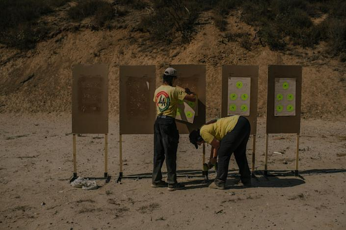 """Tom Nguyen and Robbie Tarnove of L.A. Progressive Shooters, a group that works to empower BIPOC gun owners, remove targets after a beginner's class at Burro Canyon Shooting Park in Azusa, CA.<span class=""""copyright"""">Isadora Kosofsky for TIME</span>"""