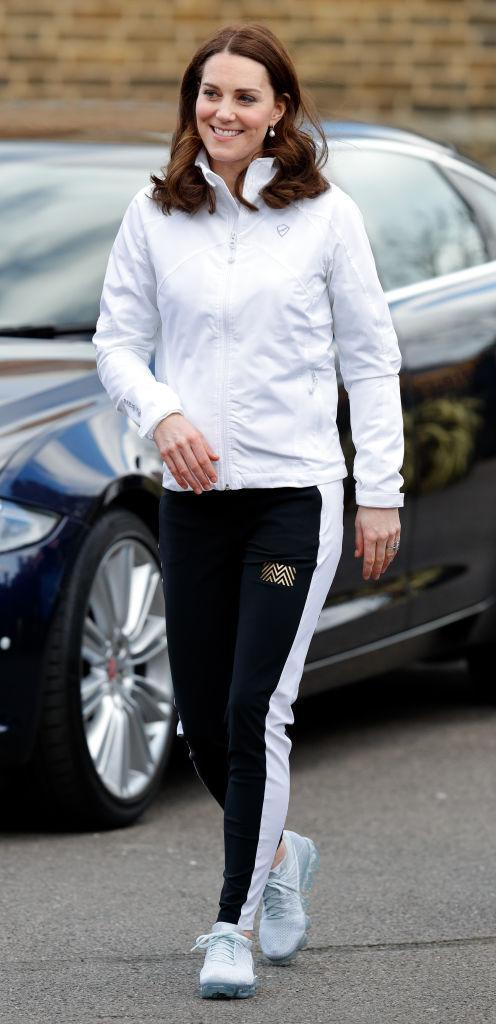 <p>The Duchess of Cambridge dressed her baby bump in a monochrome tracksuit on a recent trip to Bond Primary School in Mitcham.<br>Kate Middleton chose a £120 white jacket by Clarice and accessorised the sports-luxe aesthetic with a pair of Nike trainers. <em>[Photo: Getty]</em> </p>