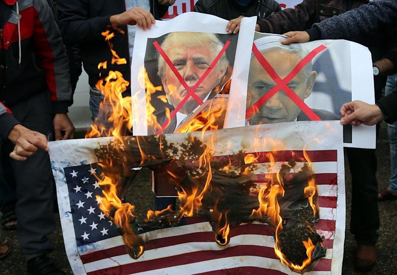 Palestinians burn posters depicting Israeli Prime Minister Benjamin Netanyahu and Trump during the Rafah protest.
