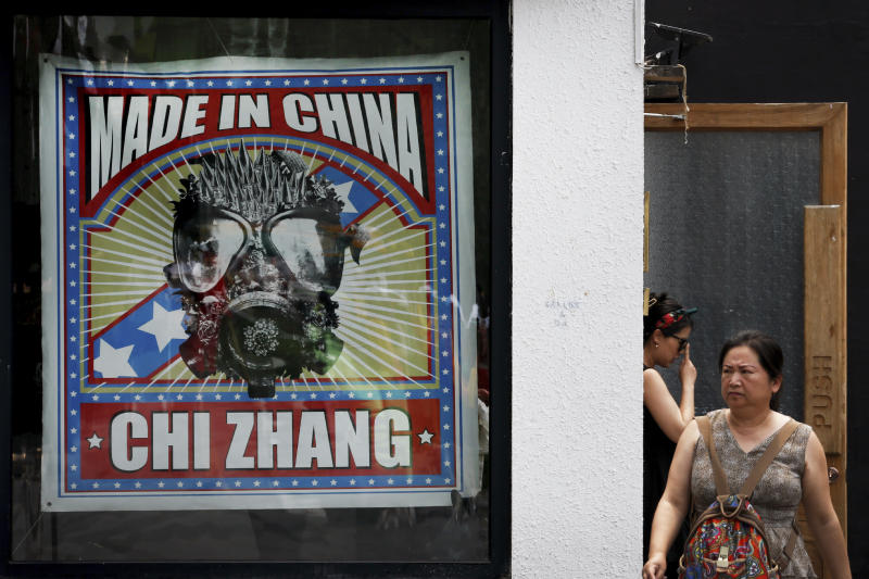 Women step out from a fashion boutique at the capital city's popular shopping mall in Beijing, Tuesday, June 25, 2019. China says its trade negotiators are talking to their U.S. counterparts on how to resolve disputes ahead of an expected meeting between their two heads of state at the G20 meeting in Japan later this week. (AP Photo/Andy Wong)