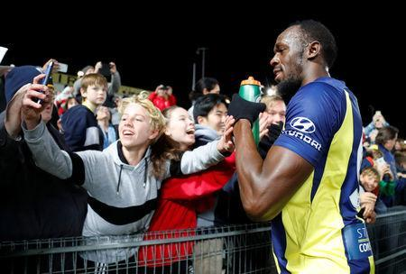 Soccer Football - Central Coast Mariners v Central Coast Select - Central Coast Stadium, Gosford, Australia - August 31, 2018 Central Coast Mariners' Usain Bolt poses for a photo with a fan after the match REUTERS/David Gray/Files