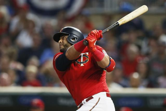 Minnesota Twins' Nelson Cruz hits a sacrifice fly off Kansas City Royals pitcher Eric Skoglund, scoring Mitch Garver in the first inning of a baseball game Friday, Sept. 20, 2019, in Minneapolis. (AP Photo/Jim Mone)