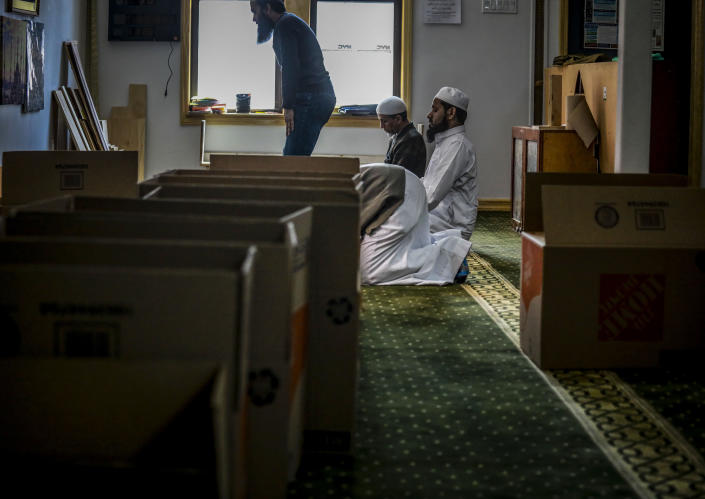 """Imam Mufti Mohammed Ismail, far right, leader of An-Noor Cultural Center and masjid for a mostly Bangladeshi Muslim community in Elmhurst, N.Y., prays with volunteers as they break from loading boxes of food supplies for those impacted by COVID-19 restrictions April 22, 2020. """"I'm receiving so many phone calls from families who are saying, 'we are not poor, but the situation has [made] it so hard, so we need a food box,"""" said Imam Ismail, who has seen increase demands on the center's resources to meet the needs of the faithful during Ramadan. (AP Photo/Bebeto Matthews)"""