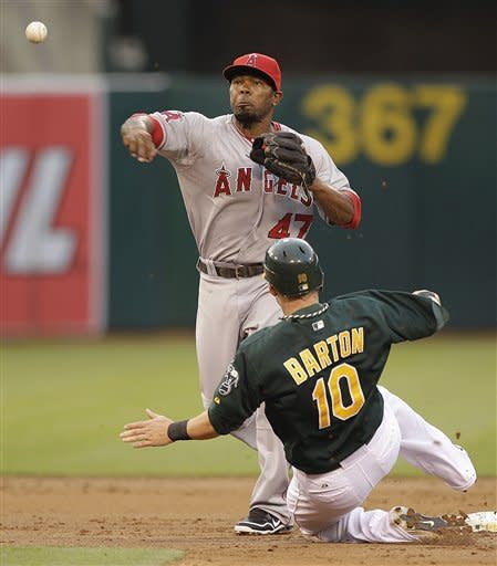 Los Angeles Angels second baseman Howie Kendrick (47) completes his double play throw to first base over Oakland Athletics' Daric Barton (10) during the second inning of a baseball game, Monday, May 21, 2012, in Oakland, Calif. A's Kurt Suzuki was out at first base. (AP Photo/Ben Margot)