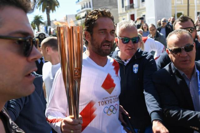 US actor Gerard Butler takes part in the Olympic flame torch relay for the Tokyo 2020 Summer Olympics