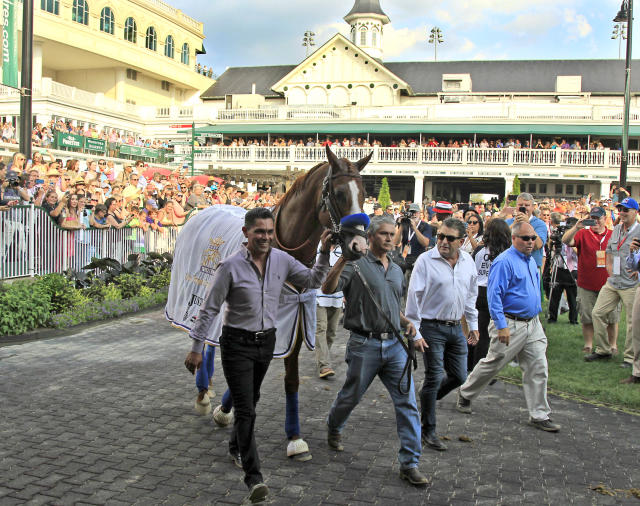 FILE - In this June 16, 2018, file photo, Triple Crown champion Justify, led by exercise rider Humberto Gomez, left, and groom Eduardo Luna, second from left, is the center of attention in the paddock at Churchill Downs in Louisville, Ky. The undefeated Triple Crown winner has been retired from racing because of fluid in his left front ankle, trainer Bob Baffert and Justifys owners announced Wednesday, July 25, 2018. They cited caution over the horses ankle making it impossible to tell if hed be able to race by the fall. (AP Photo/Garry Jones, File)