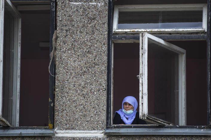 An Iraqi woman looks from a window of a building at the refugee camp in the village of Verebiejai, some 145km (99,1 miles) south from Vilnius, Lithuania, Sunday, July 11, 2021. Migrants at the school in the village of Verebiejai, about 140 kilometers (87 miles) from Vilnius, haven't been allowed to leave the premises and are under close police surveillance. Some have tested positive for COVID-19 and have been isolated in the building. (AP Photo/Mindaugas Kulbis)