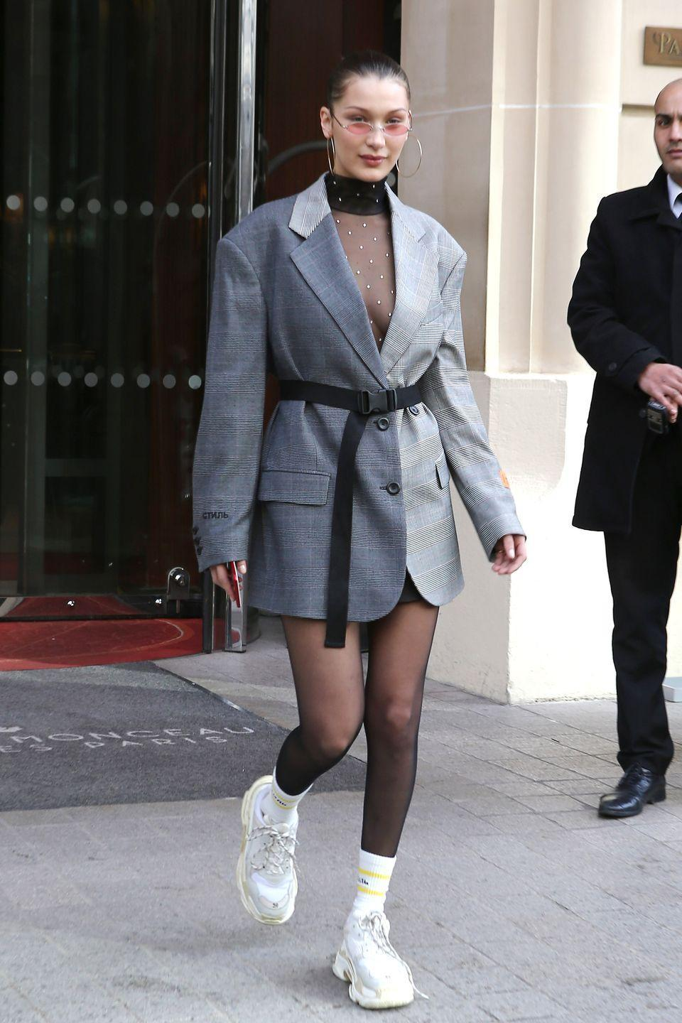 <p>In a Heron Preston studded sheer turtleneck dress, oversized blazer, and tube socks while out in Paris. The model accessorized the look with oversized hoop earrings, tiny lens sunglasses, and dad sneakers. </p>