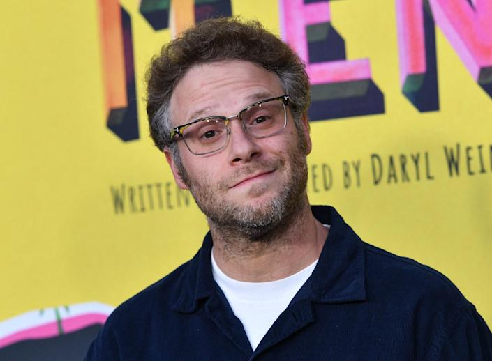 Rogen cocks his head to the side while smiling for a photo