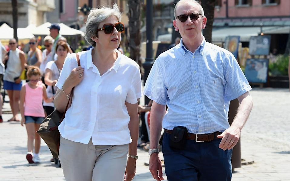 Mrs May is currently on holiday with her husband Philip - AFP