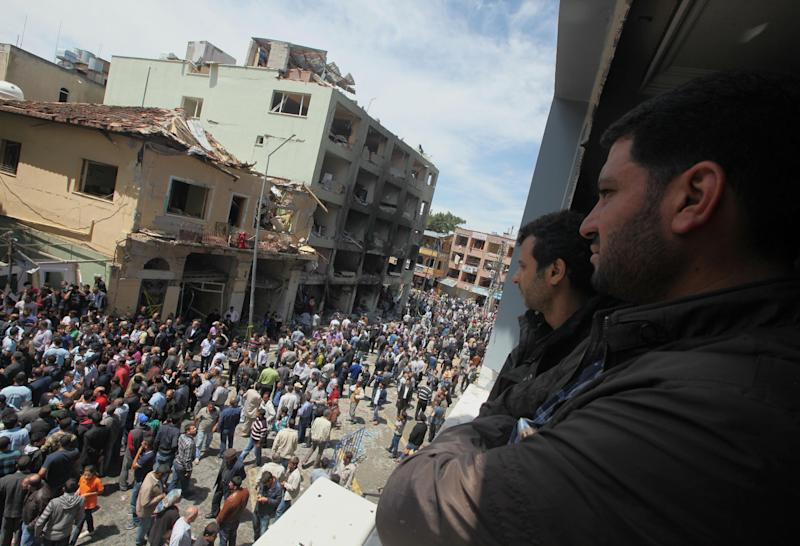People gathered at the scene at one of the Saturday explosion sites that killed tens of people, in Reyhanli, near Turkey's border with Syria, Monday, May 13, 2013. The bombings on Saturday marked the biggest incident of cross-border violence since the start of Syria's bloody civil war and has the raised fear of Turkey being pulled deeper into the conflict.(AP Photo/Burhan Ozbilici)