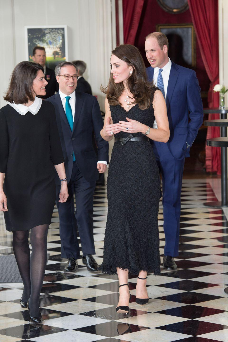 <p>In a black tweed gown with a thin leather belt, ankle strap pumps and pearl jewelry at the British Embassy in Paris.</p>