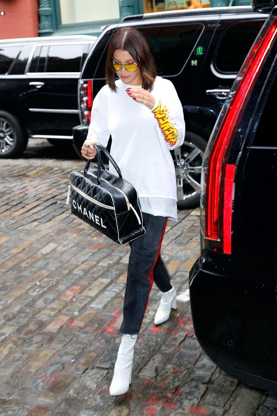 <p>In a white graphic tee with red leather striped Vetements jeans, Stuart Weitzman ankle boots, a Chanel duffel bag and yellow tinted aviator sunglasses while out in New York City.</p>