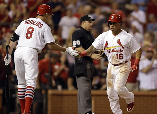St. Louis Cardinals' Kolten Wong, right, is congratulated by teammate Peter Bourjos after hitting a solo home run during the seventh inning of a baseball game against the Pittsburgh Pirates Wednesday, July 9, 2014, in St. Louis. (AP Photo/Jeff Roberson)