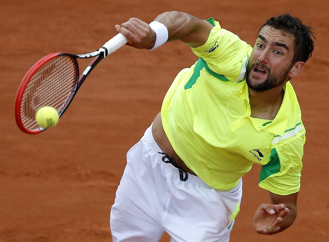 Croatia's Marin Cilic serves the ball to Serbia's Novak Djokovic during their third round match of  the French Open tennis tournament at the Roland Garros stadium, in Paris, France, Friday, May 30, 2014. (AP Photo/Michel Spingler)