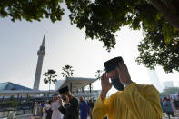 Muslims wearing protective masks pray outside the National Mosque while celebrating Eid al-Fitr, the Muslim festival marking the end the holy fasting month of Ramadan in Kuala Lumpur, Malaysia, Thursday, May 13, 2021. (AP Photo/Vincent Thian)