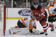 Philadelphia Flyers goaltender Carter Hart, left, and New Jersey Devils' Nico Hischier watch the puck during the second period of an NHL hockey game in Newark, N.J., Friday, Nov. 1, 2019. (AP Photo/Seth Wenig)