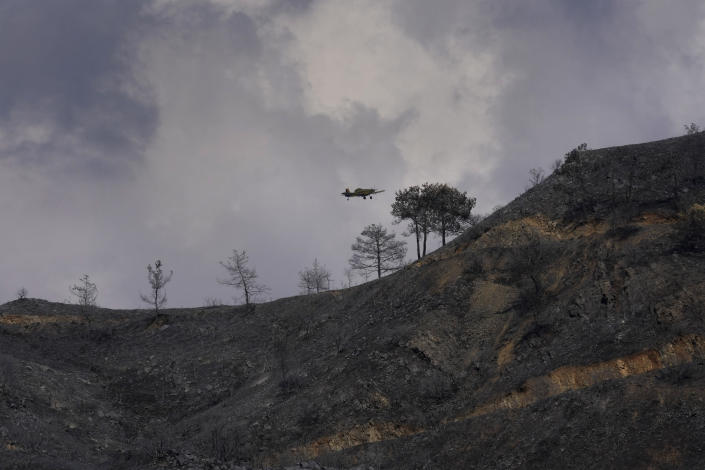 """A fighter aircraft flies over the burned Larnaca mountain region near Ora village, Cyprus, Sunday, July 4, 2021. Cyprus' interior minister says four people have died in what he called the """"most destructive"""" fire in the island nation's history. (AP Photo/Petros Karadjias)"""