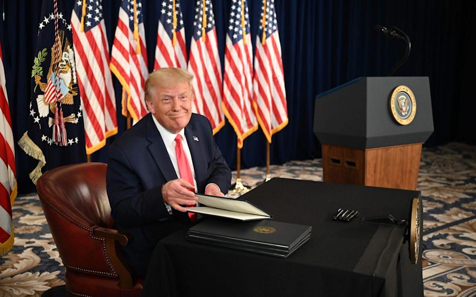 President Donald Trump signs executive orders extending coronavirus economic relief, during a news conference in Bedminster, New Jersey - JIM WATSON / AFP