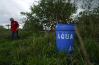 Migrant rights activist Eduardo Canales walks behind one of his blue water drops Saturday, May 15, 2021, in Falfurrias, Texas. Every week, Canales fills up blue water drums that are spread throughout a vast valley of Texas ranchlands and brush. They are there for migrants who venture into the rough terrain to avoid being caught and sent back to Mexico. (AP Photo/Gregory Bull)