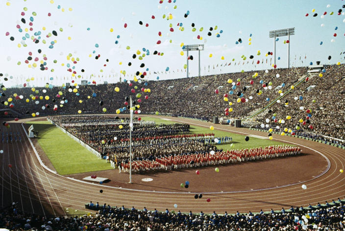 FILE - In this Oct. 10, 1964, file photo, balloons fly over Olympians and spectators during the opening ceremony of the 1964 Summer Olympics at the National Stadium in Tokyo. The famous 1964 Tokyo Olympics highlighted Japan's resiliency. It was a prospering country that was showing off bullet trains, transistor radios, and a restored reputation just 19 years after devastating defeat in World War II. Now Japan and Tokyo are on display again, attempting to stage the postponed 2020 Tokyo Olympics in the midst of a once-in-a century pandemic. (AP Photo, File)