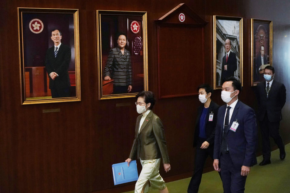 "Hong Kong Chief Executive Carrie Lam, left, arrives the chamber for her policy address in the Legislative Council in Hong Kong, Wednesday, Nov. 25, 2020. Lam said Wednesday that the city's new national security law has been ""remarkably effective in restoring stability"" after months of political unrest, and that bringing normalcy back to the political system is an urgent priority. (AP Photo/Kin Cheung)"
