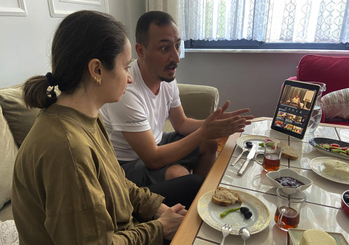 Alparslan Atas, 41, center, gestures as he talks to his wife Gulistan, 38, left, over breakfast at their home in Istanbul, while watching on a tablet, Sedat Peker, a Turkish fugitive crime boss on video, Sunday, June 6, 2021. Sunday is the day the 49-year-old convicted crime ringleader posts the latest installation of his hour-long tell-all videos from his stated base in Dubai that have captivated Turkey and turned the mobster into an unlikely social media phenomenon. The convicted crime ringleader has been dishing the dirt on members of Turkish President Recep Tayyip Erdogan's ruling party. The allegations range from drug trafficking and a murder cover-up to weapons transfers to Islamic militants. (AP Photo/Mehmet Guzel)