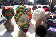 Various hats and masks are displayed on mannequin heads, Tuesday, March 9, 2021 in the Bronx borough of New York. After the virus descended on New York, the only sounds in the streets were wailing ambulance sirens. A year after the pandemic began, the nation's largest metropolis -- with a lifeblood based on round-the-clock hustle and bustle, push and pull -- is adapting and showing new life. (AP Photo/Mark Lennihan)